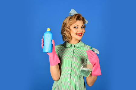 Cleanup, cleaning services, wife, gender. Housekeeper in uniform with clean spray. Pinup woman hold soup bottle. Cleaning, retro style, purity. Retro woman cleaner on blue background. Stock Photo