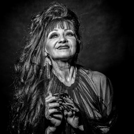 Eine alte unheimlich lächelnde Hexenfrau mit langen roten knotigen Haaren in der Bluse mit schwarzen langen Nägeln zur Hand als Halloween-Charakter mit hellem Make-up im Studio auf schwarzem Hintergrund, quadratisches Foto