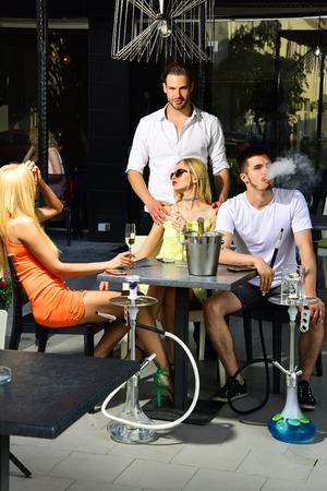 twins women and men friends relax in cafe outdoor. Man vapor hookah pipe in shisha bar lounge. Addiction, bad habits. Celebration, party concept. twins Stock Photo