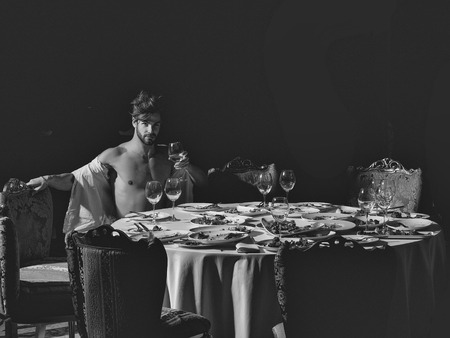 Handsome man or muscular macho athlete drinks wine from glass sitting at table with leftovers or residues food on dirty plates after banquet dinner in restaurant on dark background
