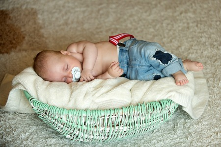 Child with pacifier asleep in crib. Newborn baby in jeans sleep in basket on floor. Childhood, infancy, innocence. Sweet dream concept. Nap, relax, tranquility. Stock Photo