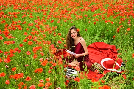 Journalism and writing, summer. Woman writer in poppy flower field. Poppy, Remembrance or Anzac Day. Opium poppy, agile business, ecology. Drug, narcotics, opium, woman with typewriter, camera, book.