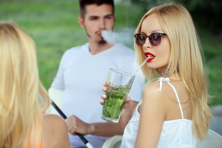 Friends at shisha cafe lounge. woman drink mojito cocktail with man. Man vaping hookah pipe with girlfriend in bar. Love, cheating, date, relationship. Bad habits, party, addiction. Stock Photo