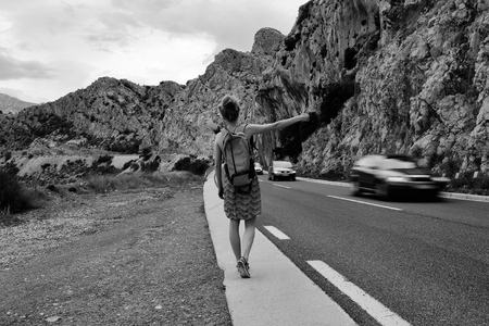 Pretty girl young woman traveler hitchhiking with thumb up hand gesture during summer vacation on mountain road