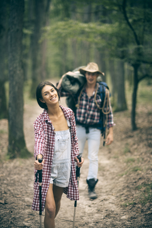 Man with woman hiking with overnight stay or picnic. Young couple with happy faces walks. Tourists concept. Couple in love hiking in forest with touristic equipment, trees on background, defocused.