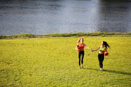Two women walking with yoga mats outside on rural area wearing sports wear and doing yoga Stock Photo