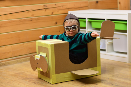 Little boy child play in cardboard plane, childhood. Kid, pilot school, innovation. Dream, career, adventure, education. Air mail delivery, aircraft construction. Pilot travel, airdrome, imagination.