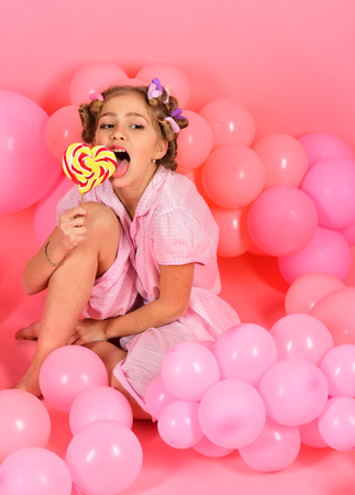 Diet, birthday, punchy pastels, beauty. Small girl child eat lollipop on pink. Childhood, happiness, sweet dreams. Little girl with candy lollipop. Party balloons, kid in curlers, pajama fashion.