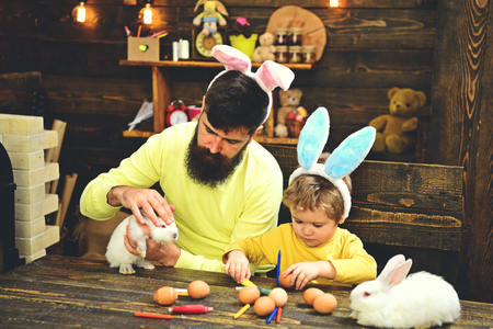Father and kid painting Easter eggs. Rabbits family with bunny ears. Cute little child boy wearing on Easter day.