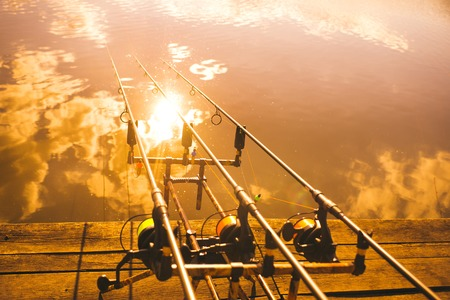 Retro toned picture of fishing equipment on wooden pier. Stock Photo