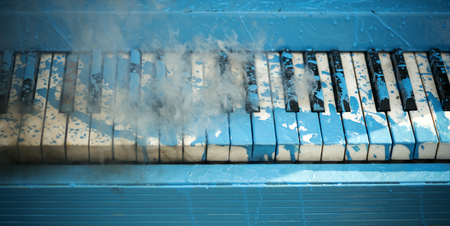 Pop and classical music, melody, rhapsody. Piano in blue paint stain, keyboard.