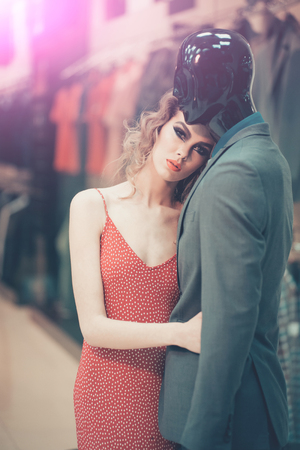 Mannequin and sensual woman in clothing shop. Mannequin in suit and fashion girl.
