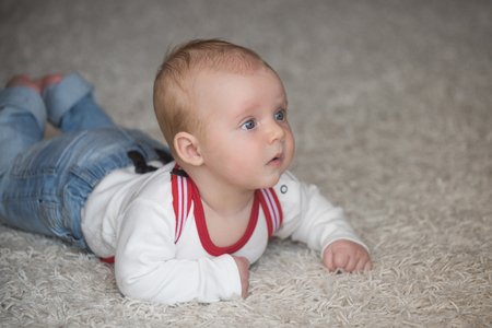 Child development concept. Infant crawl on floor carpet. Baby with blue eyes on adorable face. Innocence, beauty, purity. Childhood, infancy, newborn. 版權商用圖片 - 98375994