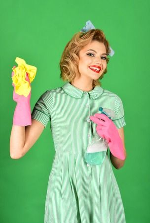 Retro woman cleaner on green background. Housekeeper in uniform with clean spray, duster. Cleanup, cleaning services, wife, gender. Cleaning, retro style, purity. Pinup woman hold soup bottle, duster.