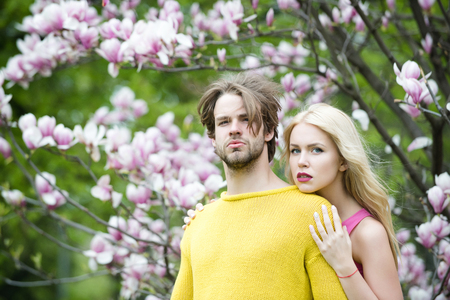Tenderness couple, flower magnolia in spring garden, beautiful nature and relationship between man and woman, harmony and understanding. Male and female hand touch pink flower. Psychology of relations