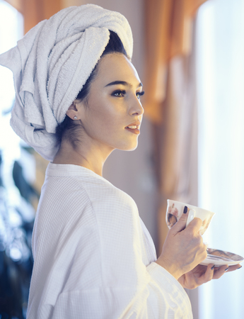 Woman in bathrobe with window on background.