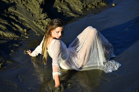 Woman relax in water on sunny day, wellness. Woman in wet dress in water stream, vacation. Summer vacation, wanderlust. Wellness, bodycare, healthcare. Fashion, beauty, look. Stok Fotoğraf