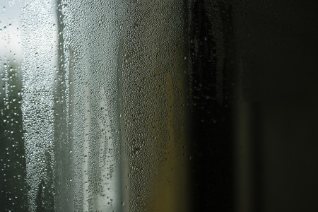 Droplets or drops of water on misted glass.