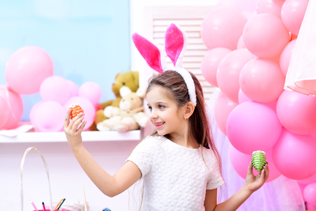 small girl paint handmade egg at party balloons. small girl with happy face hold easter eggs Stock Photo