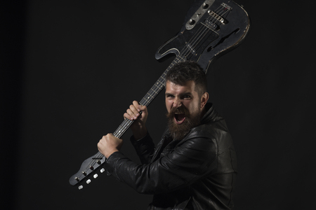 Angry man with beard hold musical instrument. Bearded man hipster with electric guitar. Music, concert, entertainment, performance, hobby. Guitar player, guitarist, musician. Rock, punk, alternative Stock Photo