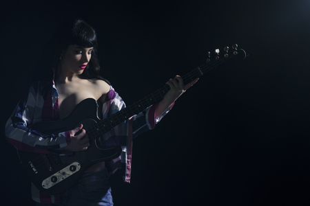 Sexy lady with brunette hair plays guitar. Woman with mysterious face in unbuttoned shirt on black background. Girl with rays of light and shadows on her body. Erotic and attraction concept.