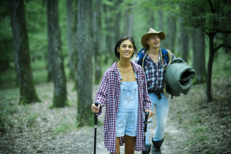 Young couple with happy faces walks. Tourists concept. Couple in love hiking in forest with touristic equipment, trees on background, defocused. Man with woman hiking with overnight stay or picnic.