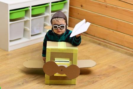 パイロット旅行、エアドローム、想像力。小さな男の子は、段ボールの飛行機、子供時代に遊びます。航空郵便配達、航空機の建設。子供、パイロ