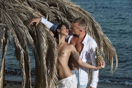 Topless woman and man kissing near umbrella made out of dried palm leaves. Couple with pineapple on vacation at tropical seashore. Love concept. Couple in love full of desire at beach, sea background.