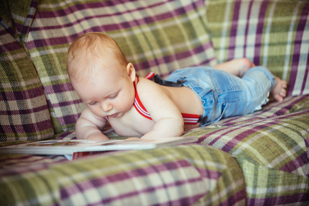 Baby boy read book on sofa. Knowledge, education, literature. Childhood, infancy, innocence. Infant wear jeans and suspenders at home. Child development concept.