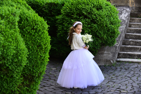Fashion, Cinderella, princess. Wedding fashion, beauty salon. Girl child in green summer park, spring. Little girl in white dress with rose flower bouquet. Bride girl, bridesmaid and wedding ceremony.