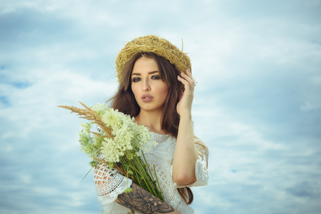 Woman with flowers cloudy sky, beauty. Woman with floral bouquet, fashion. Stok Fotoğraf