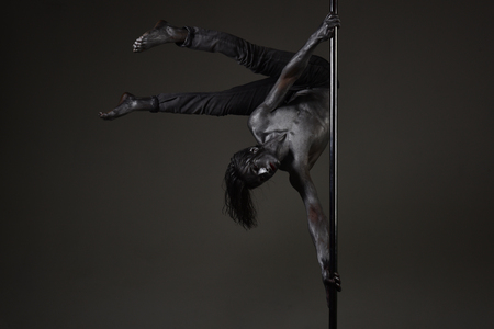 Athlete, sportsman performing pole dancing moves, work out, show trick. Guy makes figure upside down. Work out concept. Man with nude torso covered with shimmering silver paint, dark background.