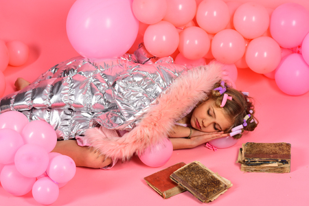 Little one year old girl sleep at old books, on pink background. Stock Photo