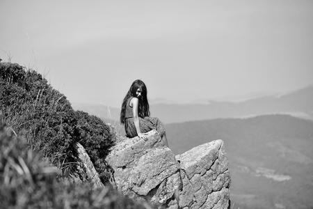 Pretty brunette smiling girl with long hair in blue lace dress sitting on stone rock cliff in beautiful landscape sunny day outdoor on natural blue sky background, horizontal photo Banco de Imagens