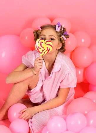 Diet, birthday, punchy pastels, beauty. Childhood, happiness, sweet dreams. Little girl with candy lollipop. Party balloons, kid in curlers, pajama fashion. Small girl child eat lollipop on pink.