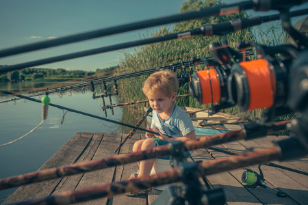Cute boy fishing fish on summer day. Banque d'images