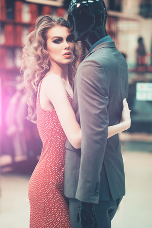 Side view of young woman hugging mannequin, perfect relationship dream concept