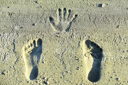 Empreinte de main et empreintes de pas sur le sable. Empreintes humaines, empreintes, traces sur une surface sablonneuse. Marques de paume, doigts, pieds, orteils. Vacances, voyages, envie de voyager. Banque d'images - 99464425