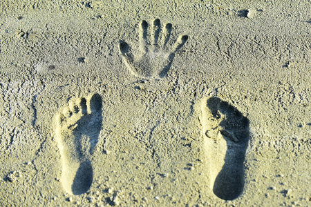 Handprint and footprints on sand. Human imprints, prints, tracks on sandy surface. Palm, fingers, feet, toes marks. Vacation, travel, wanderlust.