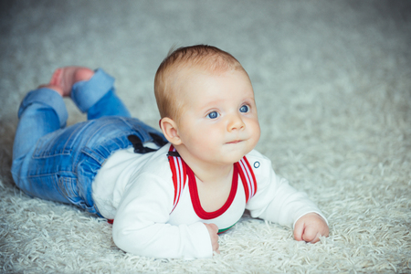 Childhood, infancy, newborn. Infant crawl on floor carpet. Child development concept. Baby with blue eyes on adorable face. Innocence, beauty, purity.