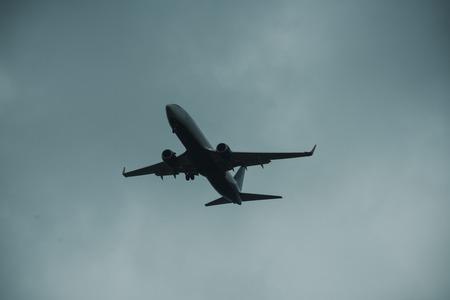 灰色の空の平面のシルエット。旅客機は空高く飛ぶ、飛行。国際線、配達、輸送。飛行と気象条件のコンセプト。