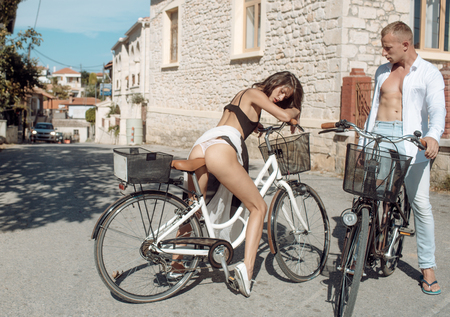 Fit and slim girl met handsome man on sunny day travelling by bicycle. Sexy couple concept. Sexy girl with naked buttocks rides bicycle, urban background. Attractive brunette sit on bicycle.
