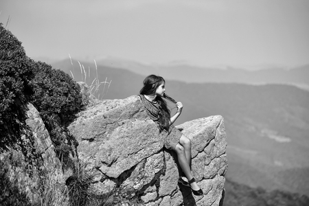 Pretty brunette pensive girl touching long hair in blue lace dress sitting on stone rock cliff looking at beautiful landscape sunny day outdoor on natural blue sky background, horizontal