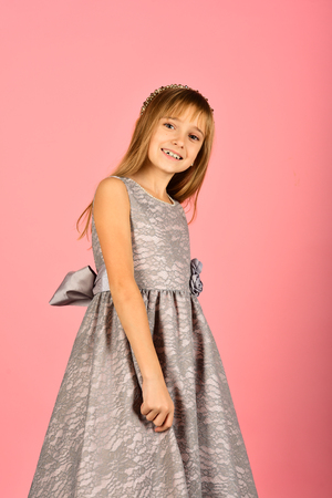 Child girl in stylish glamour dress, elegance. Look, hairdresser, makeup. Fashion model on pink background, beauty. Fashion and beauty, little princess. Little girl in fashionable dress, prom.