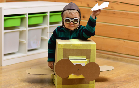 Dream, career, adventure, education. Air mail delivery, aircraft construction. Kid, pilot school, innovation. Little boy child play in cardboard plane, childhood. Pilot travel, airdrome, imagination.