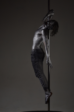 Performance concept. Man with nude torso covered with shimmering silver paint, dark background. Guy hanging on metallis pole. Athlete, sportsman performing pole dancing moves, work out, show trick. Standard-Bild - 98630476