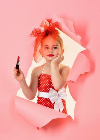 Little girl hold lipstick. little girl on pink background Stock Photo