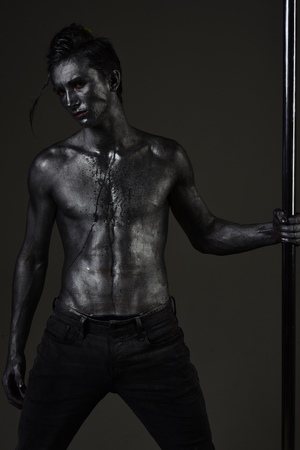 Guy puts hand on metallic pole. Man with nude torso covered with shimmering silver paint, dark background. Macho with naked chest, athlete, sportsman performing pole dancing moves. Male dancer concept