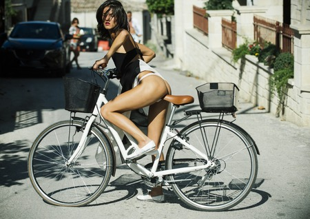 Sexy girl with naked buttocks rides bicycle, urban background. Attractive brunette sit on bicycle. Sexy tourist concept. Fit and slim girl on sunny day travelling by bicycle.
