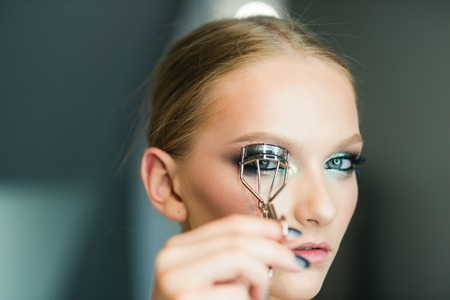 Portrait of young beautiful woman making curl eyelashes using curling cosmetic tool. Banco de Imagens